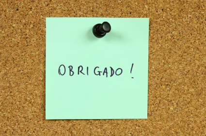 Green sticky note pinned to an office notice board. Obrigado - thank you in Portugese.