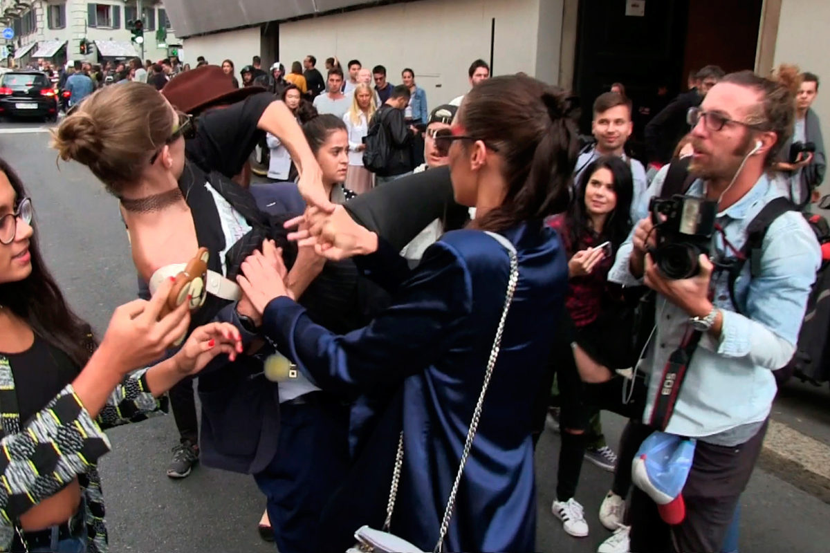 Bella and Gigi Hadid leave the Max Mara event in Milan, posing for photos with fans and smiling for the cameras. As the stunning duo made their way to their car, a crazy male fan approached Gigi from behind, picking her up off the crowd and attempting to carry her before the fiesty model fought back and sent the man running for his life. September 22, 2016 X17online.com NORTH AMERICA ONLY